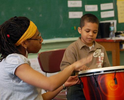 A music teacher helps a student keep the beat!