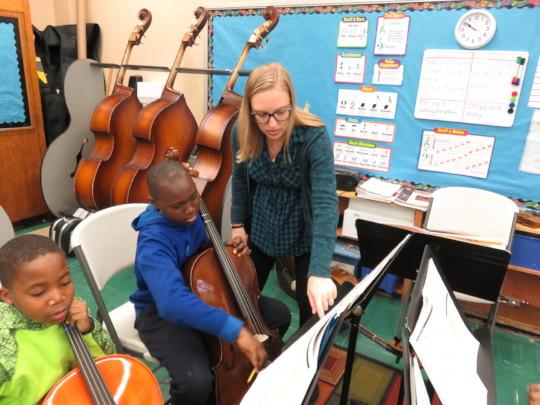An ETM music teacher instrucing a string student