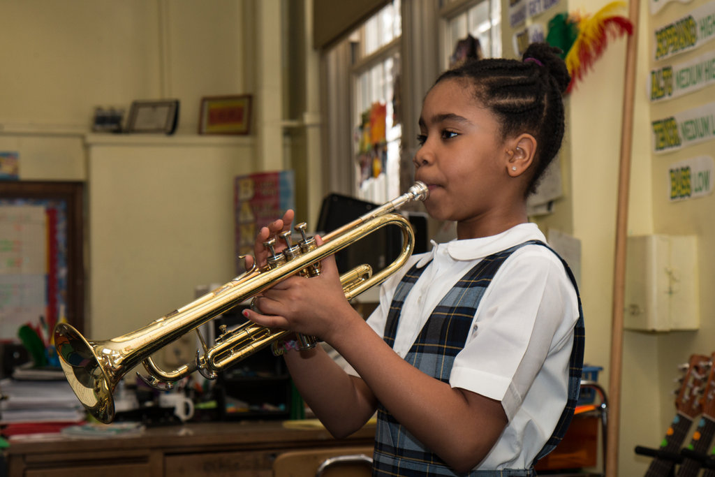 A student plays her trumpet proudly.