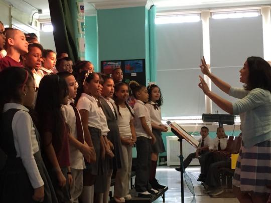 Students sing joyfully as their teacher conducts!