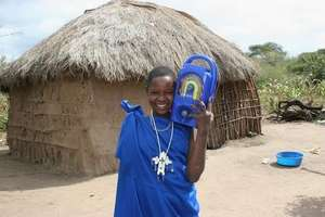 Salome with a radio outside her Masaai home