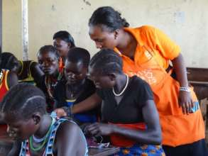 Samantha teaches girls to sew the DfG Kit
