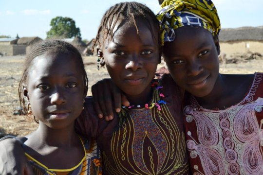 Three young girls smile in Neneko