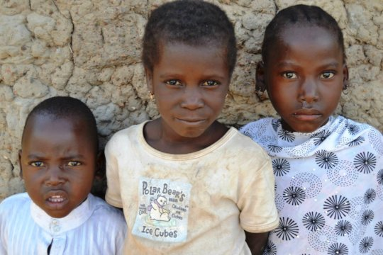 Village children take a break from school to pose