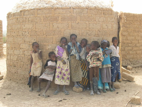 Children standing in front of cotton, stored in a mud-brick cyli