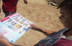 A child reads a hygiene pamphlet