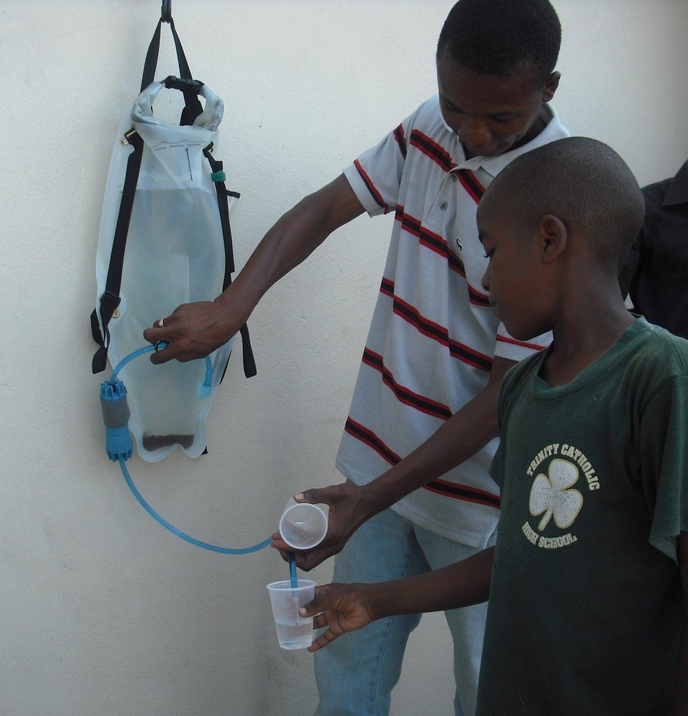 Dispensing water from a DayOne Waterbag in Haiti