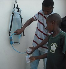 Dispensing water from a DayOne Waterbag in Haiti