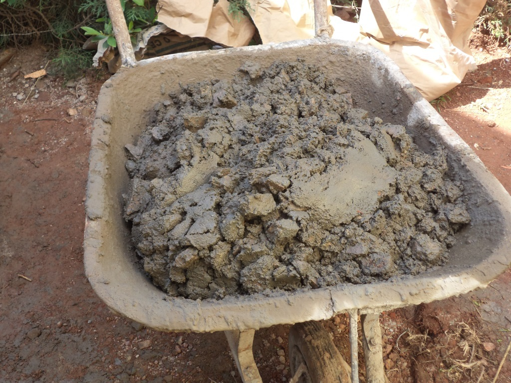 Concrete being mixed in a wheel barrow