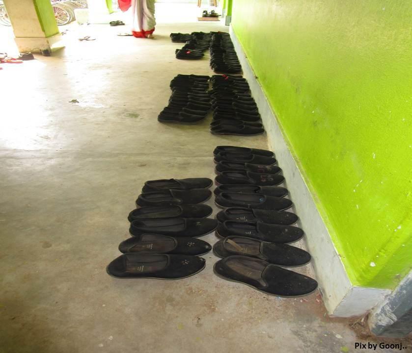Shoes neatly arranged outside a classroom..