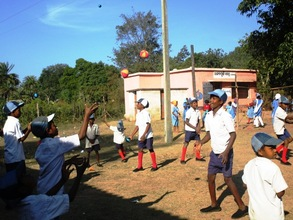 Children playing with the ball in the school kit