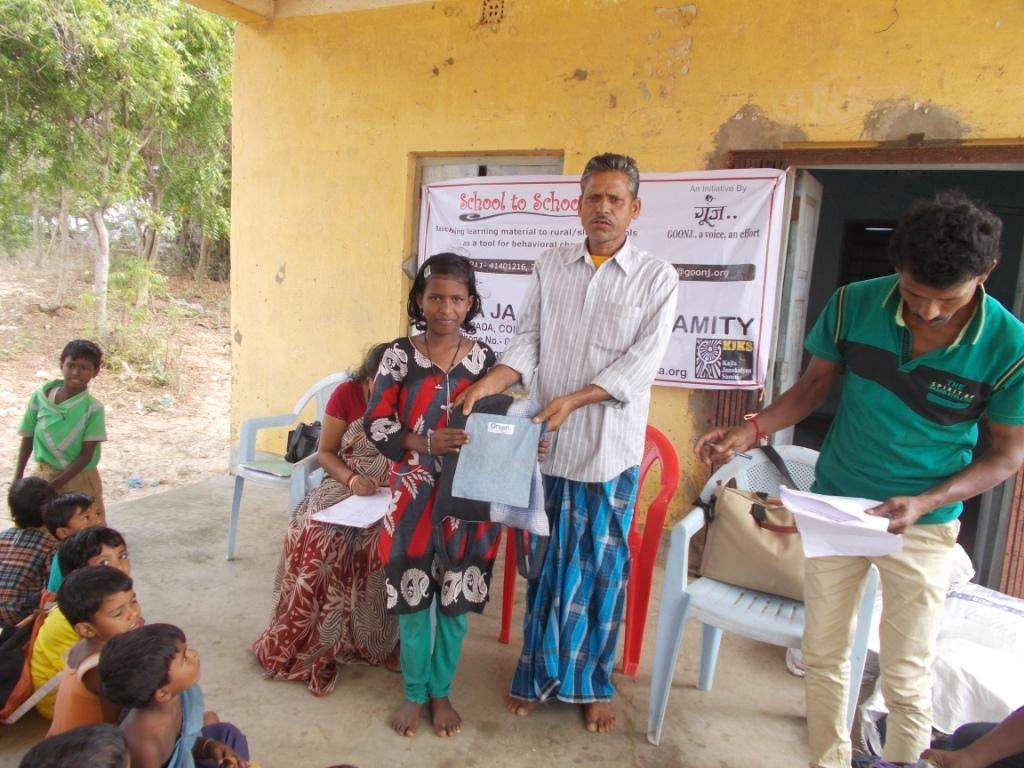Girl child receiving the school kit..