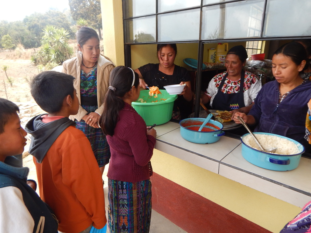 Mothers serve children lunch in new kitchen