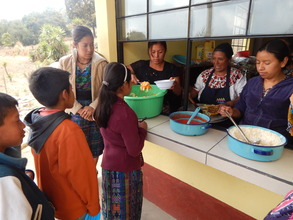 Mothers serve children lunch in new kitchen