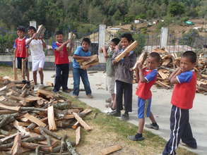 Children bring firewood to school for the stoves