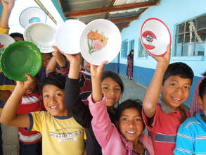 Children bring their plates to school for lunch