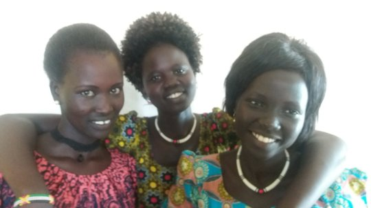 Akur, Anna, and Abuk working at the PESS office