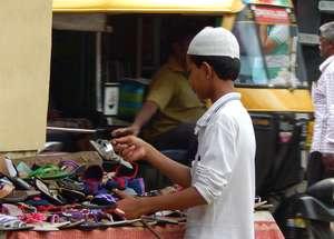 Child in a Bangalore slum selling footwear