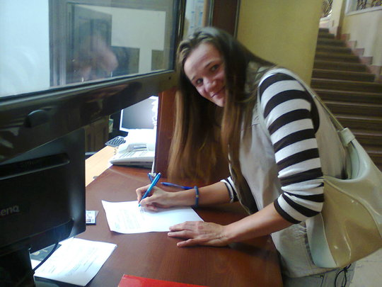 Aleksandra signing the contract for the house