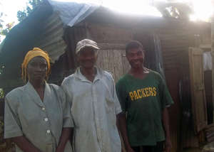 Mr. Maxi (center) outside his temporary shack.