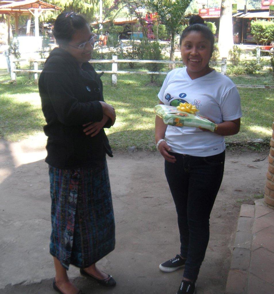 Mayra gives Juana a graduation gift.