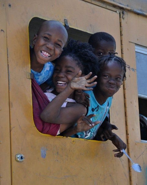 Children waving from a tap-tap bus in Haiti