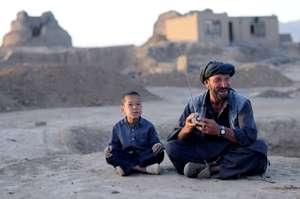 Afghan boy and man with radio: Barat Ali Batoor