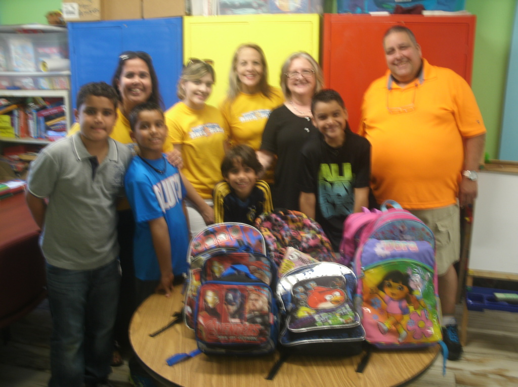 Volunteers donating back packs for school