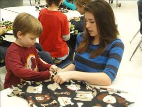 Maddie and a young volunteer maing blankets