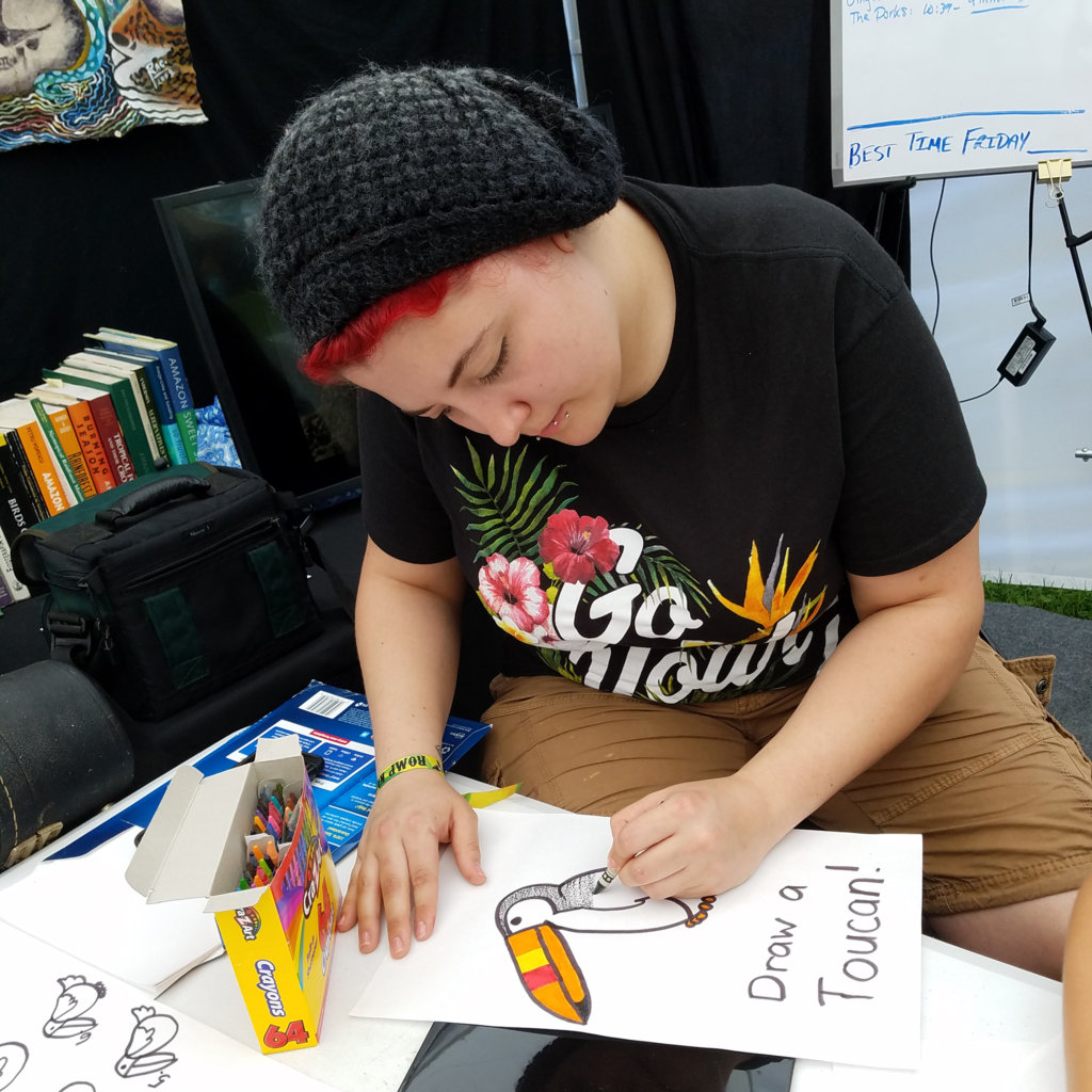 Drawing a toucan at CACE booth at festival
