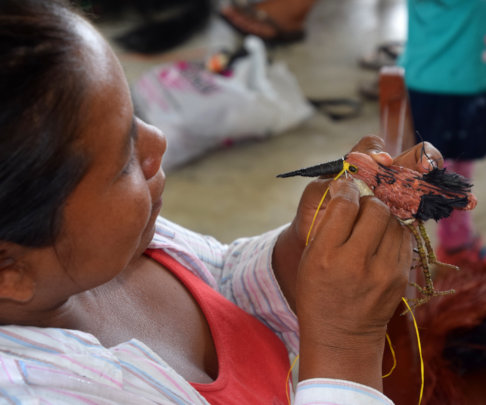Artisan sewing eye onto tiger heron ornament