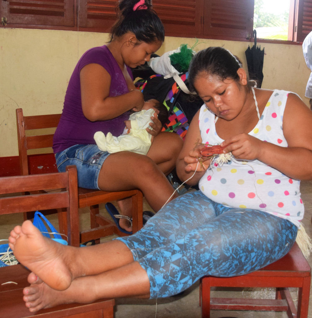 One artisan weaving; one artisan nursing