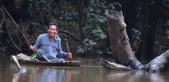 9. Smiling man fishing from dugout canoe