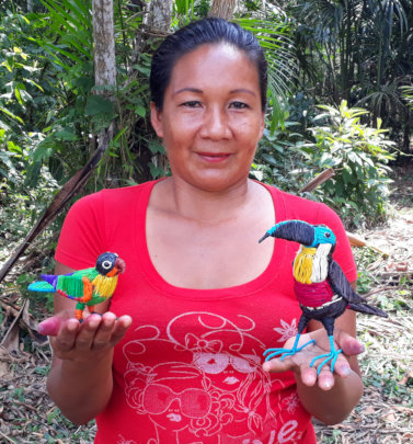 Artisan at Estiron workshop with parrot and toucan