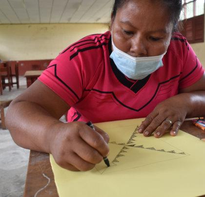 Bora artisan drawing native design on mandala