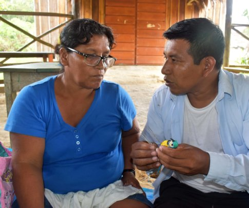Edson teaching Maijuna artisan to make a macaw
