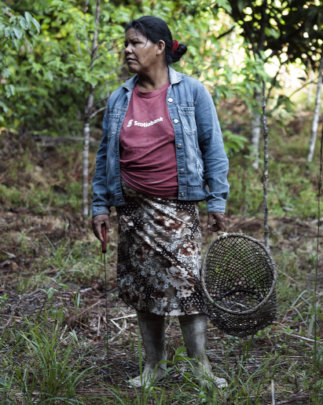 Bora woman in her field with basket and machete