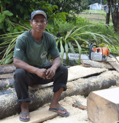 Bora man with chainsaw and wooden planks