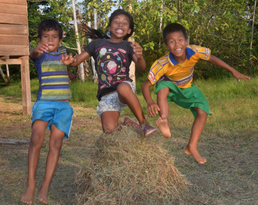 Bora children jumping over hay in Brillo Nuevo