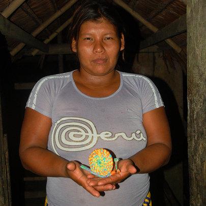 Maijuna artisan with snail ornament. Plowden/CACE
