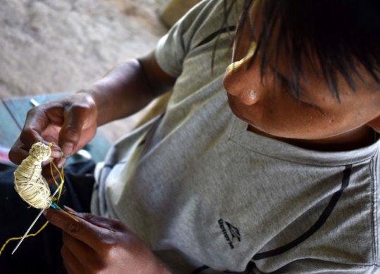 Maijuna artisan making body for bird ornament