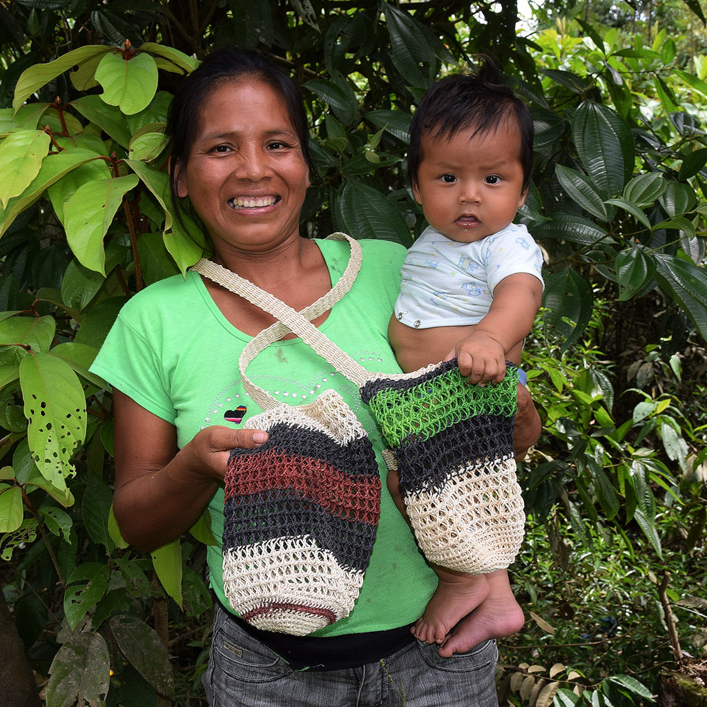 Nuevo Peru artisan with son and bottle carrier