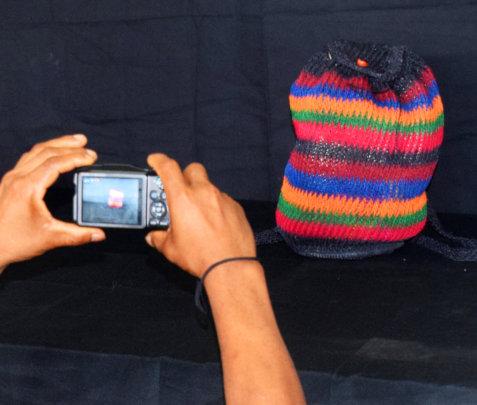 Artisan taking studio photograph of woven bag