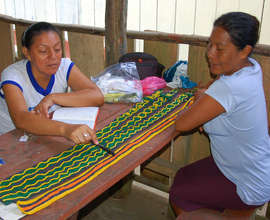 CACE manager Yully reviewing crafts with Angelina