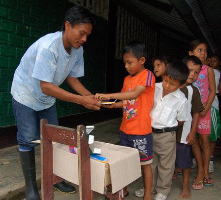Bora man distributing school supplies from CACE