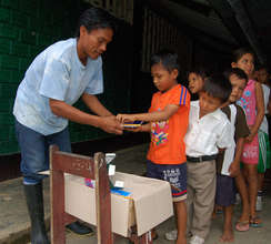 Bora man distributing school supplies from CACE