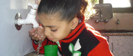 YOung girl drinking water from a Maia Unit