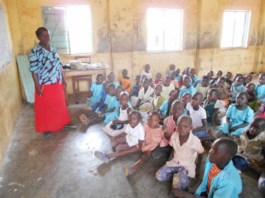 Children at school with teacher and no desks!