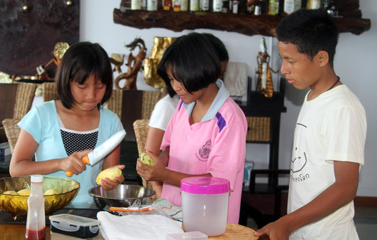 Children from SHO helping to get dinner ready