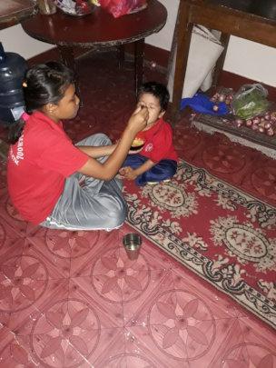 A  big girl feeding a younger